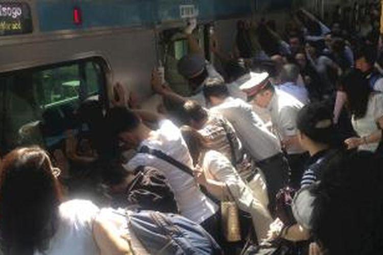 Para penumpang dan petugas kereta api mendorong sebuah gerbong kereta untuk menyelamatkan seorang perempuan yang terjebak di Stasiun Minami Urawa, Tokyo, Jepang, Selasa (23/7).