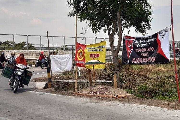 Pengguna jalan melintasi makam buatan di tepi jalan menuju fly over Tol Solo-Ngawi tepatnya di Desa Pandeyan, Kecamatan Ngemplak, Boyolali, Jawa Tengah, Selasa (20/10/2020). Makam itu dibuat oleh Raspala Desa Pandeyan sebagai peringatan pembuang sampah sembarangan.