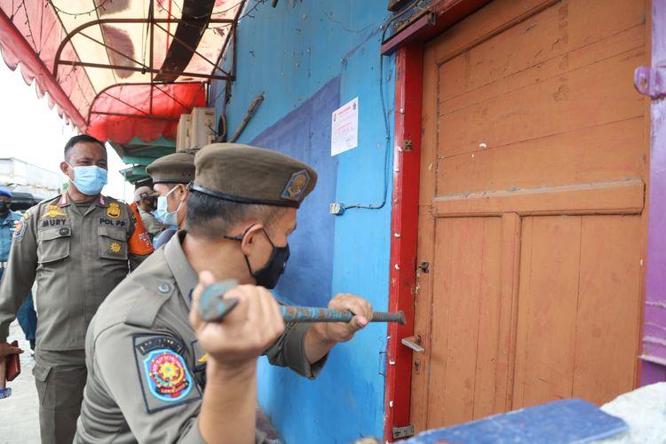 Petugas gabungan yang terdiri dari Satpol PP, TNI-Polri menyegel 25 kafe ilegal yang berdiri di atas lahan milik Pemerintah Provinsi DKI Jakarta, tepatnya di Jalan Inspeksi kali Cakung Drain dan Kali Gendong, Cilincing, Jakarta Utara pada Senin (21/12/2020).