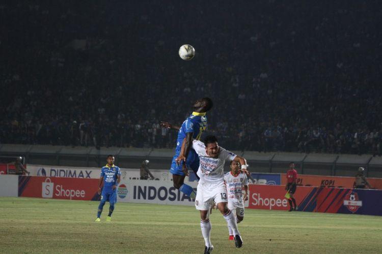 Penyerang Persib Bandung, Ezechiel N'Douassel berduel dengan bek Bali United, Gunawan Dwi Cahyo, pada laga Persib vs Bali United di Stadion Si Jalak Harupat, Jumat (26/7/2019) malam.