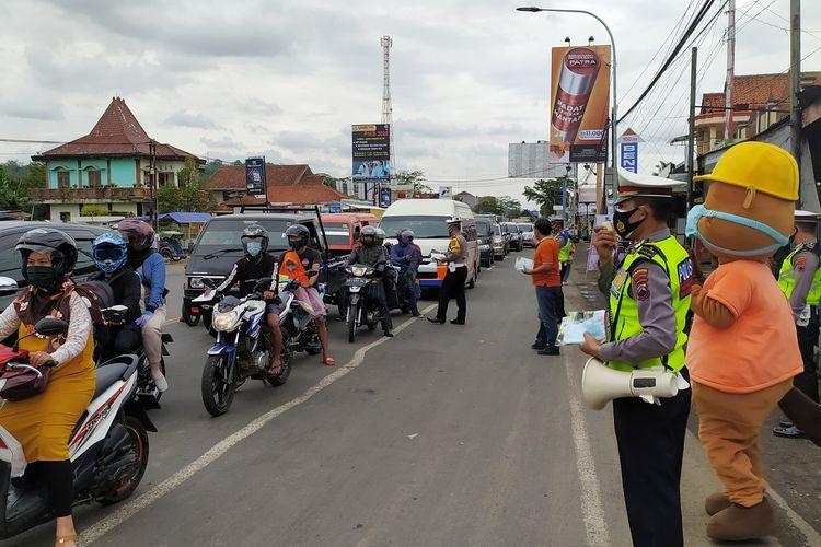 Polisi membagikan masker dan memberikan imbauan mengenai protokol kesehatan kepada pengguna jalan di simpang empat Buntu, Banyumas, Jawa Tengah, Sabtu (2/1/2021).