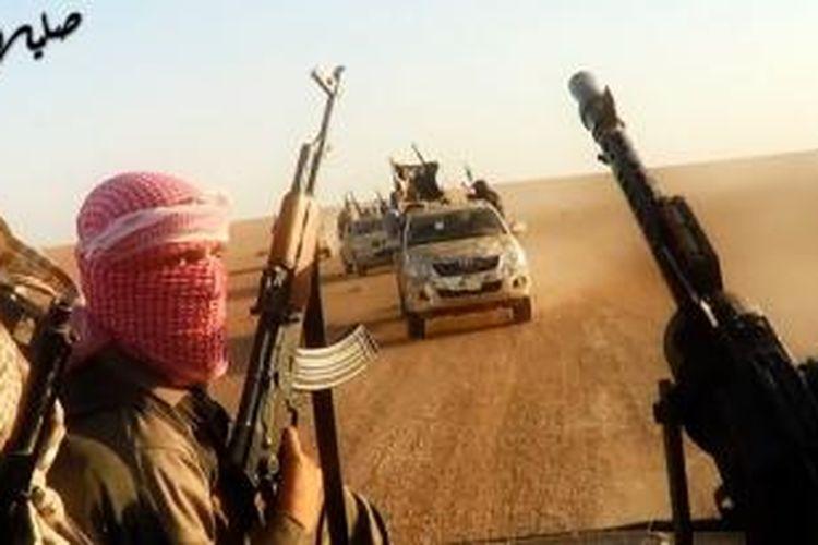 Foto ini diambil dari sebuah video propaganda yang diunggah ke internet pada 8 Juni 2014 oleh kelompok Negara Islam Irak dan Suriah (ISIS) memperlihatkan para pejuang kelompok itu menaiki kendaraan bak terbuka di dekat kota Tikrit, Irak, Rabu (11/6/2014). Pasukan ISIS berkonvoi setelah sebelumnya merebut kota Mosul dari tangan pasukan pemerintah Irak.