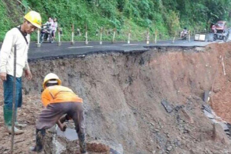 Dua orang pekerja sedang membersihkan material longsor di Desa Bandungsari, Banjarharjo, Brebes, Jawa Tengah.