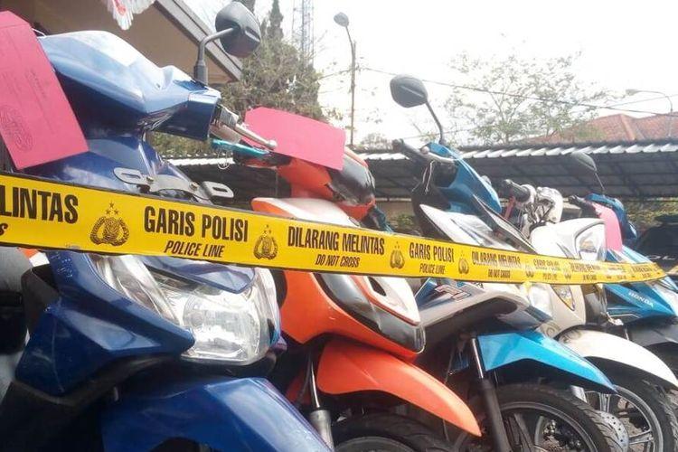 Seorang anggota polisi melintas di antara deretan sepeda motor hasil kejahatan yang diekspose di halaman Polsek Pacet, Cianjur, Jawa Barat, Kamis (20/8/2020). Terkait kasus curanmor tersebut polisi meringkus dua orang pelaku.