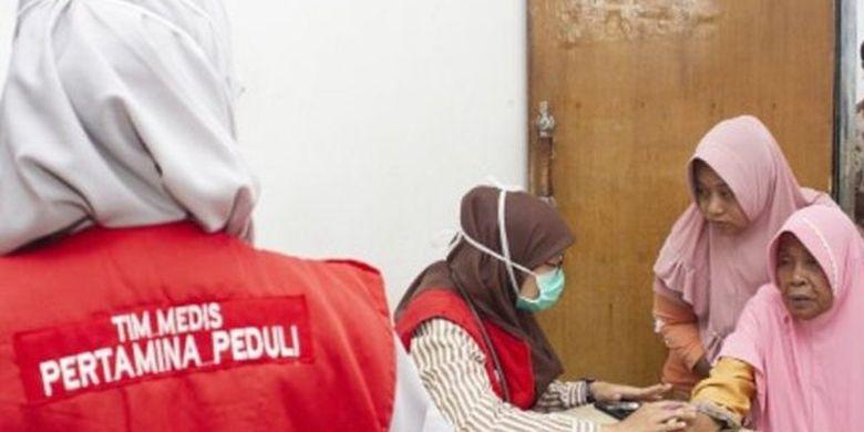 Tim medis Pertamina Peduli memeriksa kesehatan warga di Posko layanan kesehatan, Cemarajaya, Karawang, Jawa Barat, Rabu (7/8/2019)