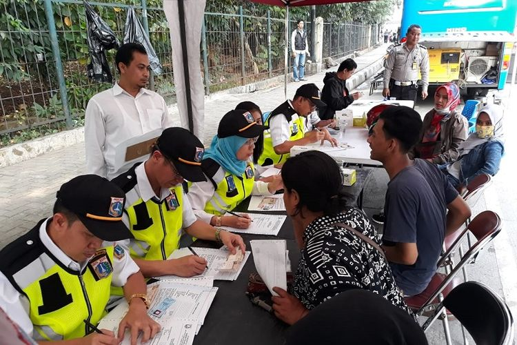 Sejumlah penunggak pajak kendaraan mengurus surat pernyataan membayar pajak setelah terkena razia pajak kendaran di Jalan DI Panjaitan, Jakarta Timur, Rabu (25/7/2018). Mereka  diberikan waktu tiga hari untuk melunasi tunggakan. Bila tidak juga membayar, nomor pelat kendaraan mereka akan diblokir.