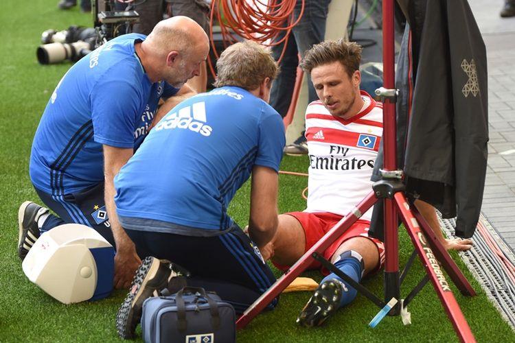Gelandang Hamburg SV, Nicolai Mueller, mendapatkan perawatan akibat cedera dalam pertandingan perdana Bundesliga 2017-2018 melawan FC Augsburg di Hamburg, Minggu (20/8/2017).