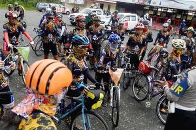 Peserta Jelajah Sepeda Kalimantan mendengarkan arahan dari polisi seusai beristirahat di pinggiran Kabupaten Banjar saat menempuh etape pertama dengan rute Banjarmasin-Rantau sejauh 118 kilometer, Senin (4/5/2015).