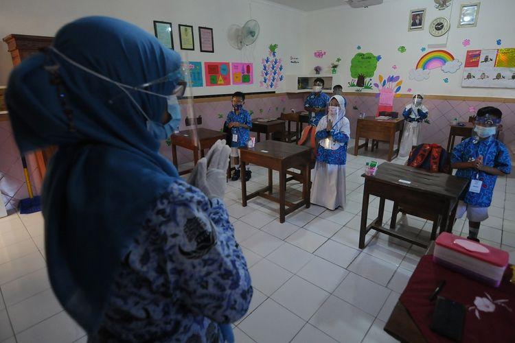 Sejumlah siswa memberi salam kepada gurunya di SD Negeri Dukuh 1, Salatiga, Jawa Tengah, Rabu (17/3/2021). Simulasi protokol kesehatan COVID-19 di sekolah tersebut tersebut bertujuan untuk memperkuat kebiasaan baru di lingkungan sekolah baik siswa dan guru agar siap dalam kegiatan belajar dan mengajar yang menerapkan pertemuan tatap muka. ANTARA FOTO/Aloysius Jarot Nugroho/aww.