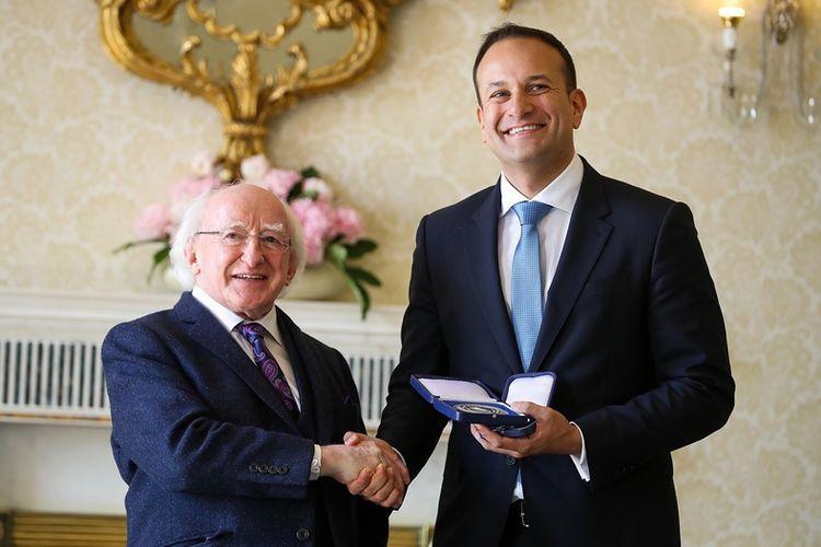 Presiden Irlandia Michael Higgins (kiri) menyalami perdana menteri yang baru Leo Varadkar saat menerimanya di Aras an Uachtarain, kediaman resmi presiden di Dublin.