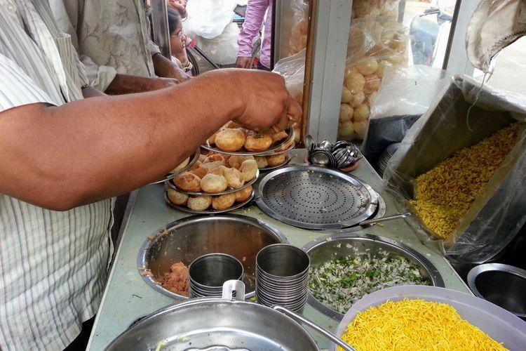 Ilustrasi penjaja street food di India membuat pani puri atau golgappa.