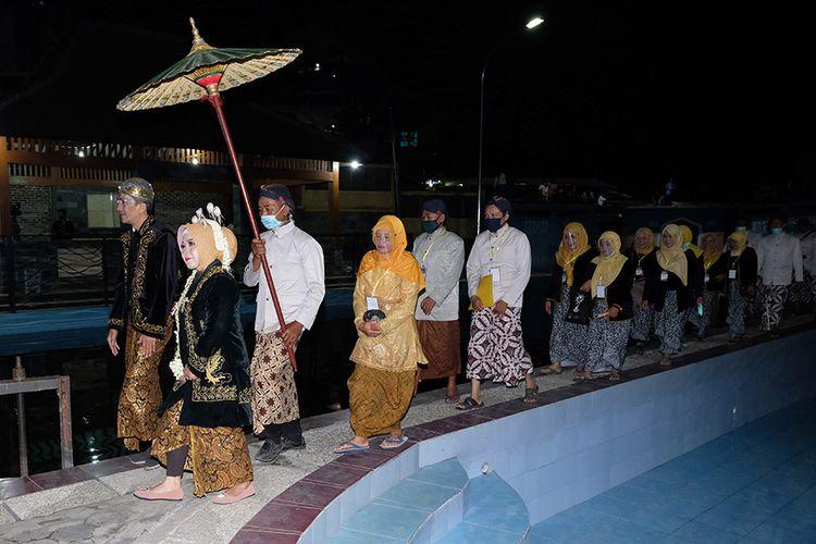 Sejumlah warga mengikuti tradisi malam satu Suro di kompleks sendang Sidhukun Desa Traji, Parakan, Temanggung, Jawa Tengah, Rabu (19/8/2020). Tradisi menyambut satu Suro yang biasanya dihadiri ribuan orang, kali ini hanya dihadiri puluhan warga tertentu dan pemangku adat karena pandemi Covid-19 dan disiarkan secara virtual.