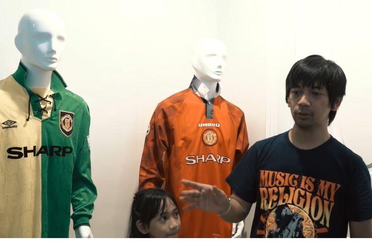 Rian D'Masiv sedang memperlihatkan koleksi jersey Manchester United yang pernah dikenakan oleh salah satu legendanya, Eric Cantona.