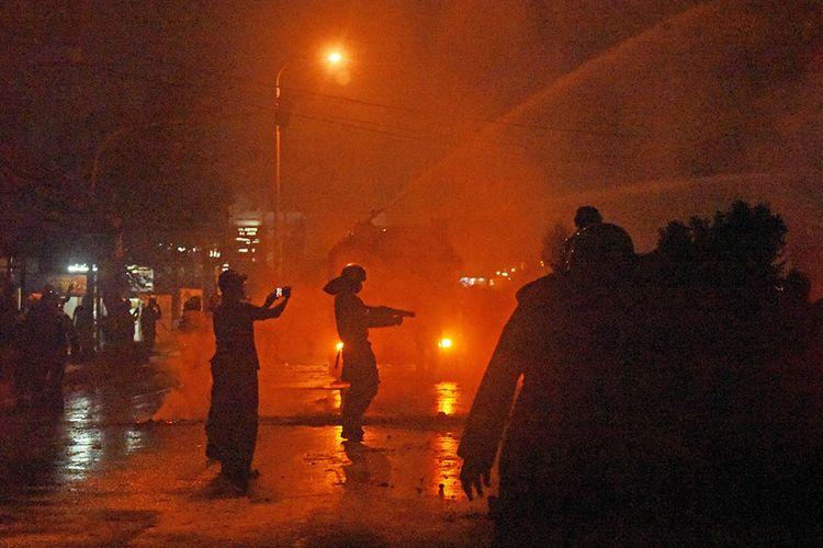 Sejumlah personel Polisi Anti Huru-hara (PHH) Polda Banten dibantu kendaraan taktis water cannon melepas tembakan gas air mata saat membubarkan aksi unjuk rasa yang menolak pengesahan Omnibus Law Undang-undang Cipta Kerja di Ciceri di Serang, Rabu (6/10/2020) malam. Polisi membubarkan para demonstran karena bertindak anarkis memblokade jalan protokol hingga larut malam dan melempari petugas dengan batu dan petasan.