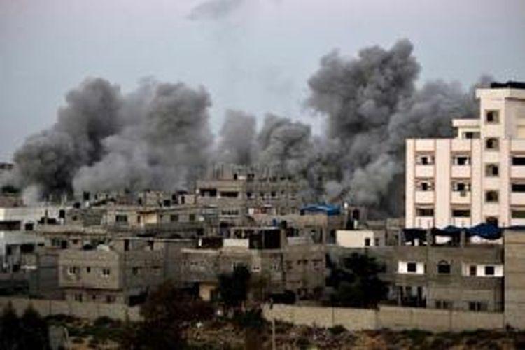 Asap mengepul setelah roket milik militer Israel menghantam sebuah gedung di kota Gaza, 9 Juli 2014. Serangan Israel menewaskan setidaknya 24 orang.