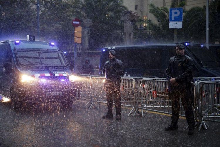 Petugas kepolisian lokal Catalonia, atau biasa disebut Mosso dEsquadra,  berdiri menjaga demonstran warga Catalonia pro-kemerdekaan di depan delegasi pemerintah Spanyol di Barcelona, 19 Oktober 2017.