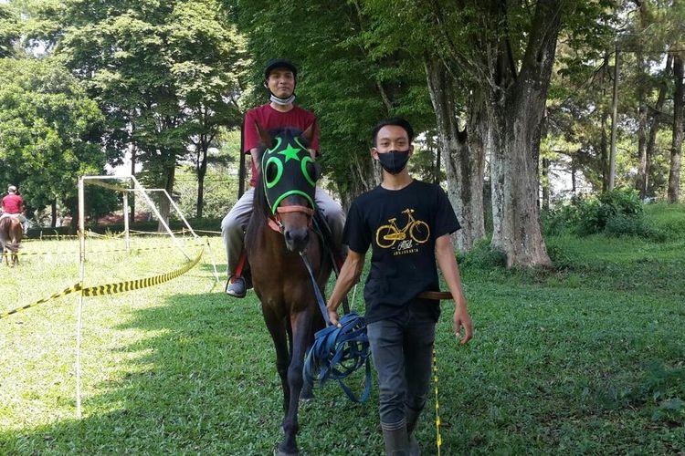 Seorang pengunjung belajar menunggangi kuda di Sekolah Berkuda Wisata Selorejo, Kabupaten Malang, Sabtu (21/11/2020).