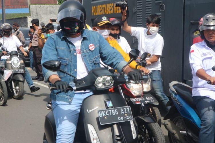 Muhammad Bobby Afif Nasution dan Aulia Rachman bersama rombongan partai pengusung konvoi menaiki Vespa menuju KPU Kota Medan untuk mendaftarkan diri sebagai bakal pasangan calon wali kota dan wakil wali kota Medan, Jumat (4/9/2020)