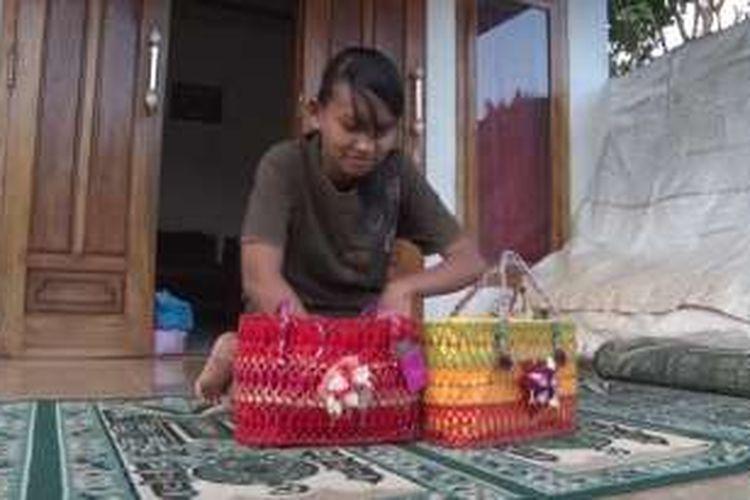 Siti Mufida tengah menyelesaikan tas dari bahan gelas plastik bekas di Desa Bogoran, Kecamatan Kampak, Kabupaten Trenggalek, Jawa Timur.