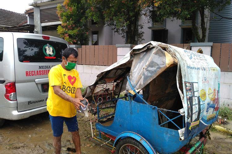 Jamot Sihite membersihkan becak motornya yang sempat terbawa banjir besar di perumahan De Flamboyan di Kelurahan Tanjung Selamat, Kecamatan Medan Tuntungan pada Kamis malam hingga Jumat dini hari (4/12/2020).