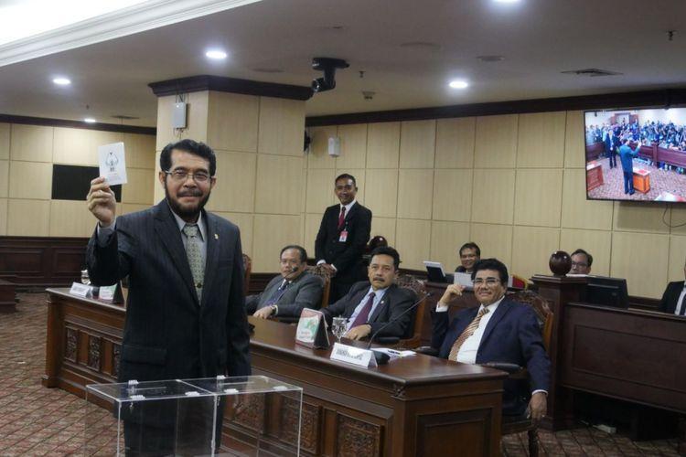 Hakim Konstitusi Anwar Usman menunjukkan surat suara pemilihan Ketua MK periode 2018-2020 di Gedung MK, Jakarta, Senin (2/4/2018)