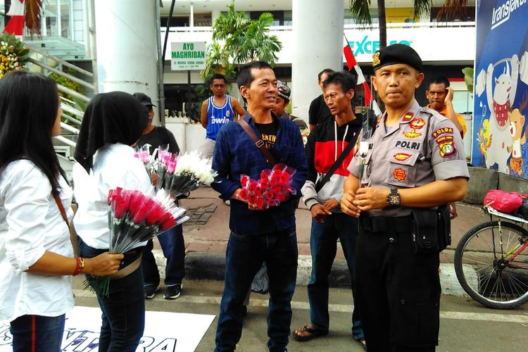 Masyarakat dari Spartan Nusantara bagikan 1.000 tangkai bunga kepada TNI-Polri di Depan Gedung Bawaslu, Jakarta Pusat pada Minggu (26/05/2019).