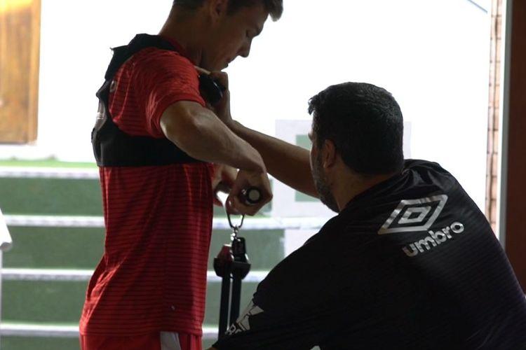Pelatih kebugaran RCD Mallorca, Dani Pastor, sedang memasang sensor dalam sesi latihan di pusat kebugaran.