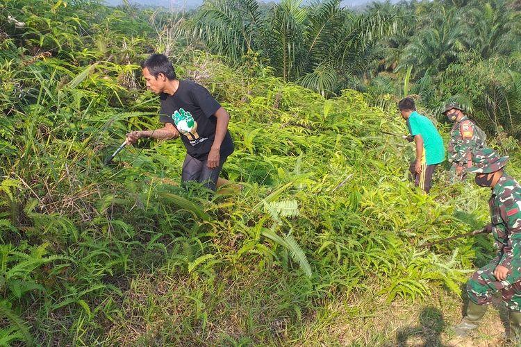 Prajurit TNI bersama warga menebas semak belukar untuk membuka jalan buat akses para petani dan menuju lokasi wisata di Desa Koto Ranah, Kecamatan Kabun, Kabupaten Rohul, Provinsi Riau, Selasa (2/3/2021). Kegiatan TNI ini dalam rangka melaksanakan Program TMMD ke 110.