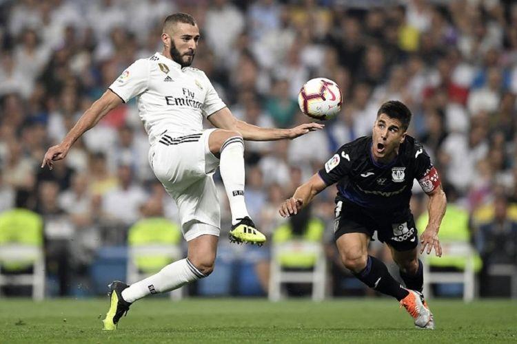 Unai Bustinza mencoba menghentikan pergerakan Karim Benzema saat Leganes berhadapan dengan Real Madrid di Stadion Santiago Bernabeu, 1 September 2018.
