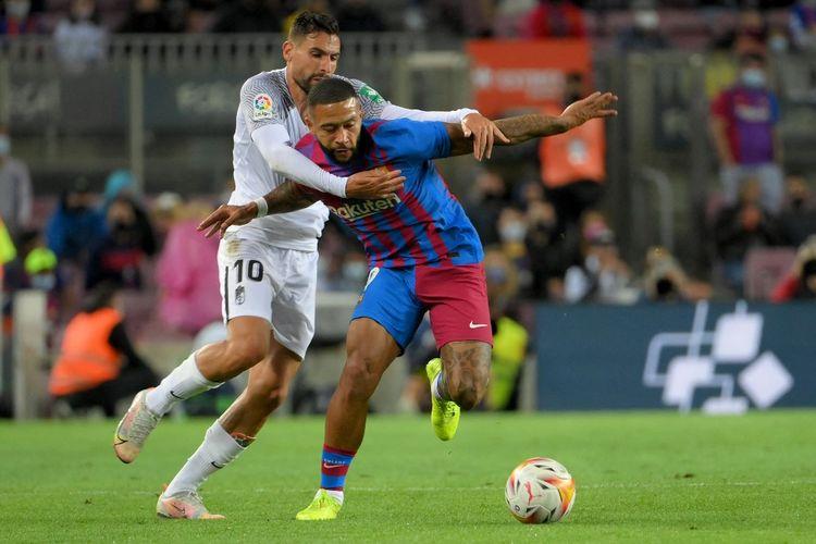 Memphis Depay (kanan) dan Antonio Puertas berebut bola dalam laga pekan kelima Liga Spanyol 2021-2022, Barcelona vs Granada, di Stadion Camp Nou, Selasa (21/9/2021) dini hari WIB.