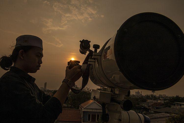 Petugas Masjid Al-Musyariin mengamati posisi hilal menggunakan teropong saat Rukyatul Hilal di Jakarta Barat, Selasa (21/7/2020). Pemantauan hilal yang dilakukan menggunakan teropong tersebut memastikan Idul Adha 1441 H jatuh pada 31 Juli 2020.