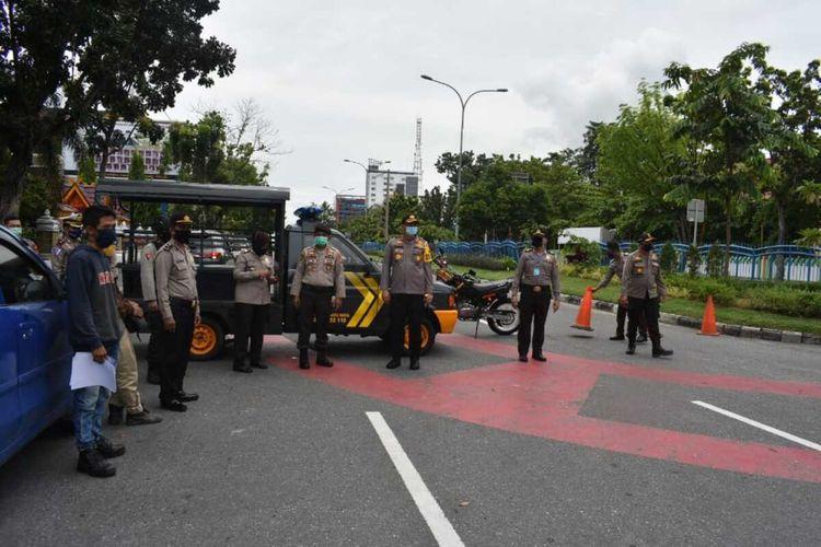 Personel Polresta Pekanbaru menutup akses Jalan Jenderal Sudirman saat penerapan PSBB di Kota Pekanbaru, Riau, untuk mencegah wabah virus corona.