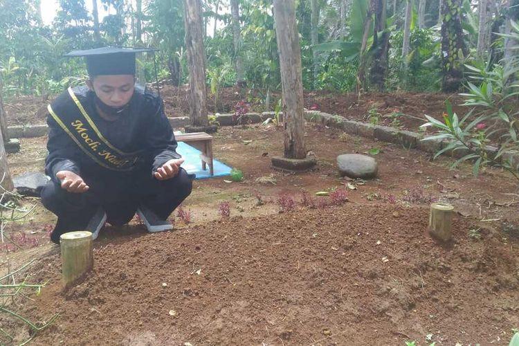 Mochamad Nadif Nasrulloh (23), mahasiswa IAIN Purwokerto mengikuti prosesi wisuda virtual di makam ayahnya di Kabupaten Banjarnegara, Jawa Tengah, Selasa (24/11/2020).