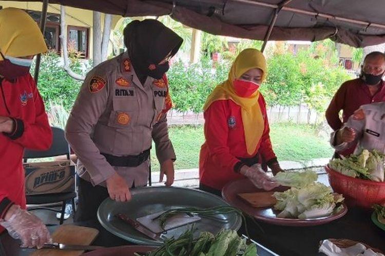 Kapolres Tegal Kota AKBP Rita Wulandari bersama Kepala Dinas Kesehatan dr. Sri Prima Indraswari menyiapkan langsung makanan bagi warga isolasi mandiri, di dapur umum yang didirikan di halaman Mapolres Tegal Kota, Minggu (20/6/2021)