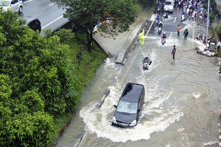 Suasana ketika sebuah mobil menerobos banjir yang terjadi di sekitar kawasan TB Simatupang, Jakarta Selatan, Senin (12/1/2014). Banjir ini terjadi akibat curah hujan yang tinggi di kawasan ibukota yang terjadi sejak Minggu malam (11/1/2014).