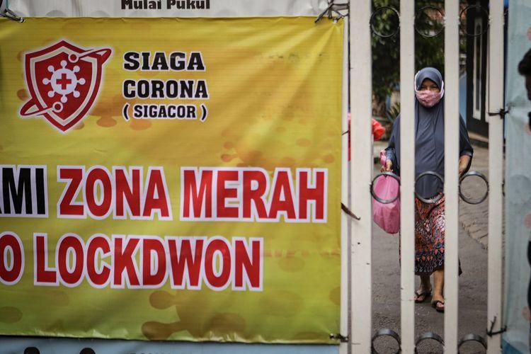 Seorang warga berjalan di kawasan yang menerapkan lockdown skala mikro di Kelurahan Gandasari, Jatiuwung, Kota Tangerang, Banten, Selasa (8/6/2021). Pemerintah setempat menerapkan lockdown skala mikro setelah 57 warga di RW03 Kelurahan Gandasari,  Jatiuwung, terkonfirmasi positif COVID-19 yang tertular saat libur lebaran. ANTARA FOTO/Fauzan/nz