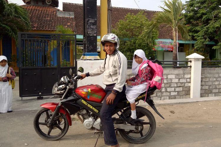 Salah seorang anggota yayasan berkas, saat menjalankan tugas mengantar siswi yatim-piatu ke sekolah.