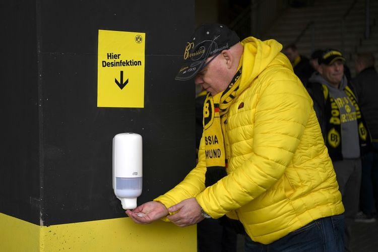 Seorang suporter membersihkan tangannya pada pertandingan sepak bola Bundesliga antara Borussia Dortmund vs SC Freiburg pada 29 Februari 2020 di Dortmund.