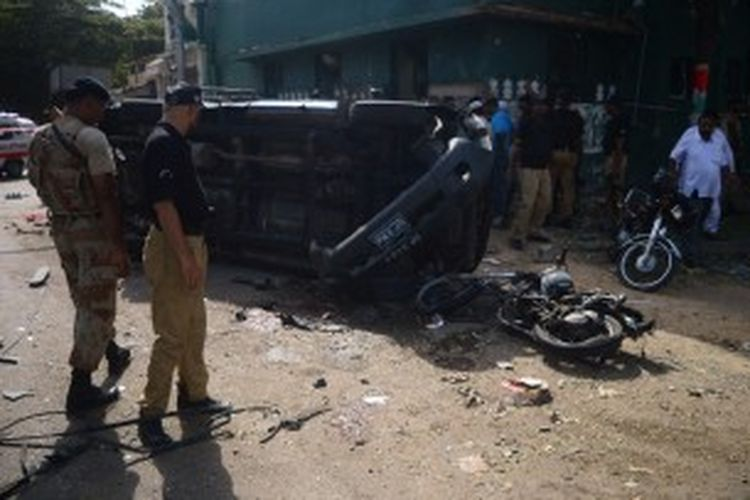 Aparat kepolisian Pakistan memeriksa mobil polisi yang hancur akibat bom yang ditujukan untuk seorang hakim ternama di kota Karachi, Rabu (26/6/2013). Tujuh orang tewas akibat ledakan bom itu, namun sang hakim lolos dari maut meski mengalami luka serius.