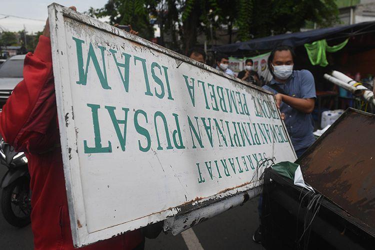Petugas membongkar atribut-atribut saat melakukan penutupan markas  DPP Front Pembela Islam (FPI) di Petamburan, Jakarta, Rabu (30/12/2020). Polisi dan TNI menutup markas FPI setelah pemerintah memutuskan untuk membubarkan organisasi pimpinan Rizieq Shihab itu.