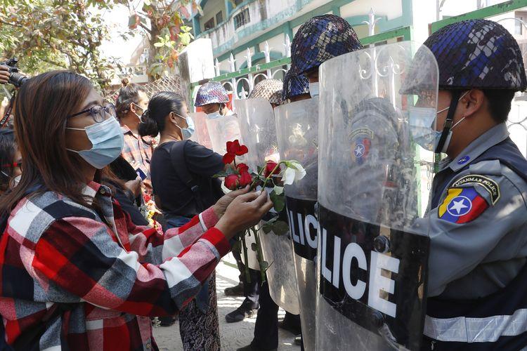 Sejumlah orang memberikan bunga mawar ke polisi, ketika empat aktivis yang ditahan hadir dalam sidang di Mandalay, Myanmar, pada Jumat (5/2/2021). Ratusan guru dan murid turun ke jalan menuntut militer mengembalikan kekuasaan ke para politisi terpilih.