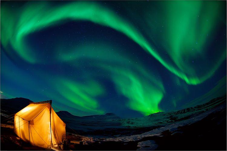 Ilustrasi mendirikan tenda di bawah langit berpanorama aurora borealis.