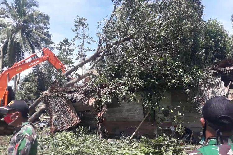 TNI Kodim 1403 Sawerigading menurunkan alat berat dan mesin pemotong kayu untuk membersihkan rumah yang tertimpa pohon akibat puting beliung di Desa salu pao, Kecamatan Lamasi Timur, Selasa (16/02/2021)