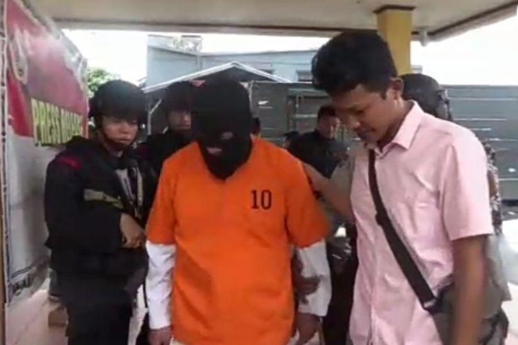 Polisi saat menggiring dokter gadungan ke ruang tahanan setelah dilakukan press release, Jumat (18/10/2019)