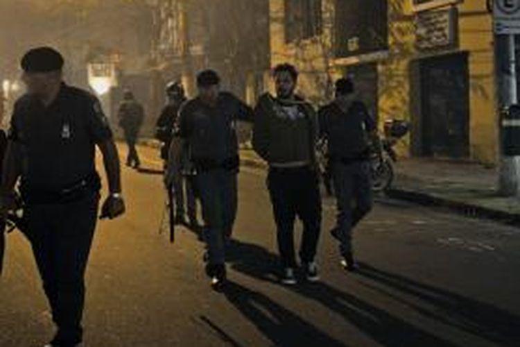 Polisi menahan seorang pengunjuk rasa di Sao Paulo, Brasil, Selasa (30/7/2013) malam waktu setempat. Polisi bertindak tegas setelah para pengunjuk rasa menyerbut bank, pertokoan, dan lokasi bisnis lain di kota tersebut.