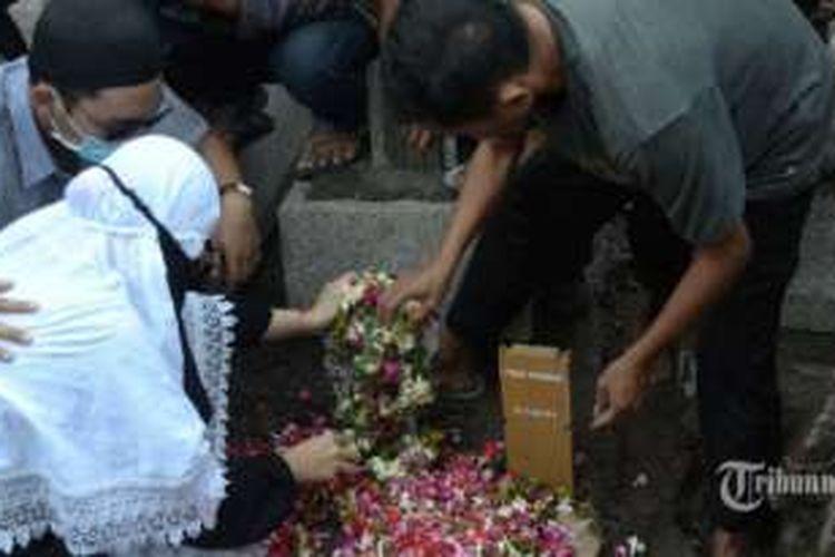 Sejumlah kerabat melakukan tabur bunga di makam Freddi Budiman di TPU Kalianak, Surabaya, Jumat (29/7). Freddi Budiman merupakan 4 dari 14 terpidana hukuman mati yang telah di eksekusi Jumat dini hari, pelaku merupakan terpidana kasus kepemilikan 1,4 juta butir ekstasi.