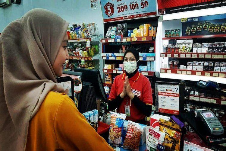 Karyawan Alfamart menggunakan masker untuk mengikuti protokol PSBB