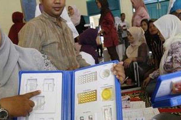 Petugas Penyuluh Lapangan Keluarga Berencana (PLKB) Kota Banda Aceh memperlihatkan jenis alat dan obat kontrasepsi kepada warga