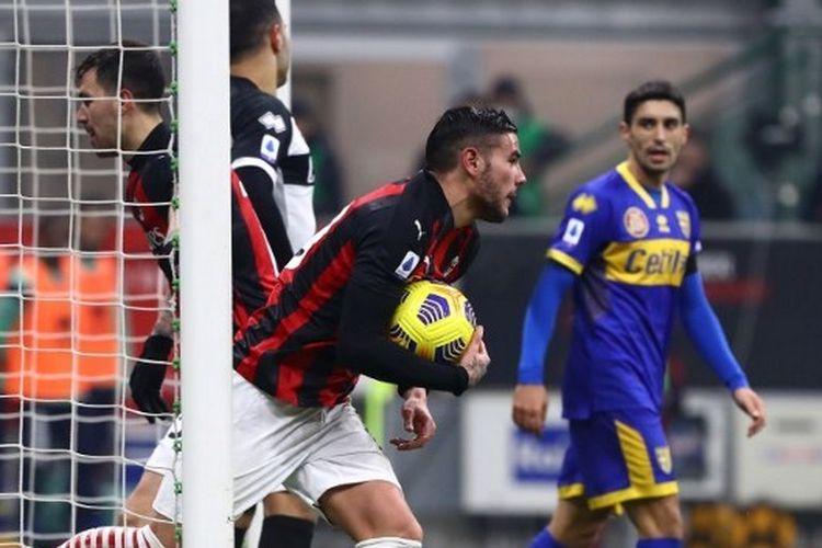 Pemain AC Milan, Theo Hernandez, memungut bola dari gawang tim tamu usai menjebol gawang Parma, Senin (14/12/2020) dini hari WIB di San Siro.