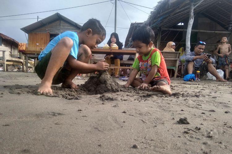 Anak bermain pasir di Pantai Ujong Blang, Kota Lhokseumawe, Aceh, Sabtu (8/6/2019)